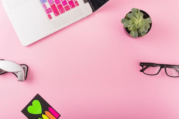 Ordenador portátil; perforadora; planta en maceta y gafas sobre fondo rosa