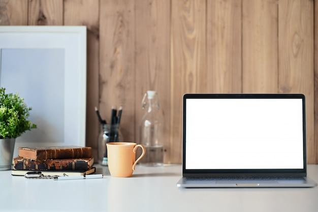 Ordenador portátil que muestra la pantalla en blanco en un escritorio de madera blanco con un cartel blanco y accesorios