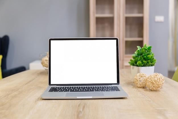 Ordenador portátil que muestra la pantalla en blanco en la mesa de trabajo vista frontal en casa