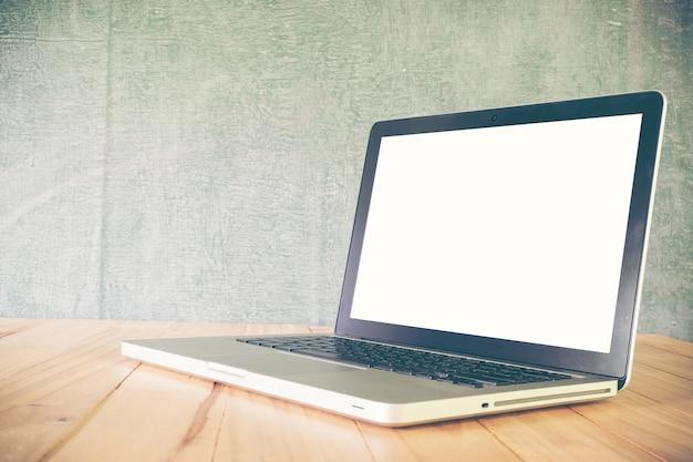 Ordenador portátil en la tabla, en el fondo de la pizarra, pantalla en blanco
