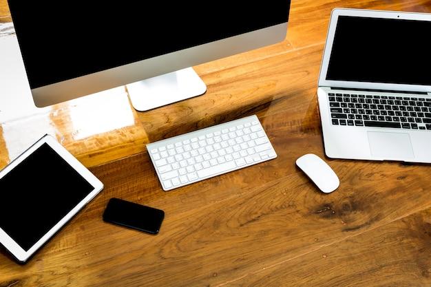 Ordenador, portátil y tablet vista desde arriba en una mesa de madera