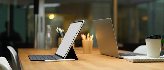 Ordenador portátil y tableta digital con teclado en la mesa de madera en la sala de reuniones, trazado de recorte.