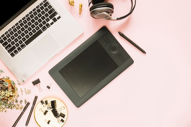 Ordenador portátil y tableta gráfica digital con auriculares en fondo rosa