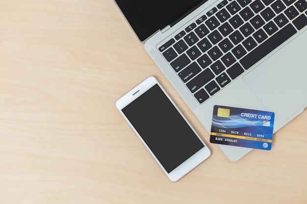 Ordenador portátil de la tarjeta de crédito de smartphone en la tabla de madera, objeto comercial, concepto en línea del trabajo.