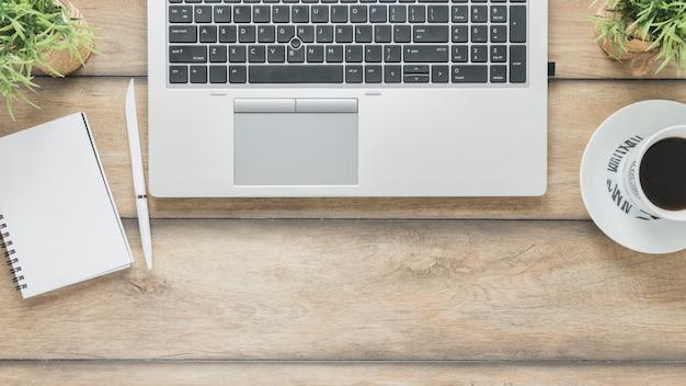 Ordenador portátil y taza de café cerca del cuaderno en la mesa