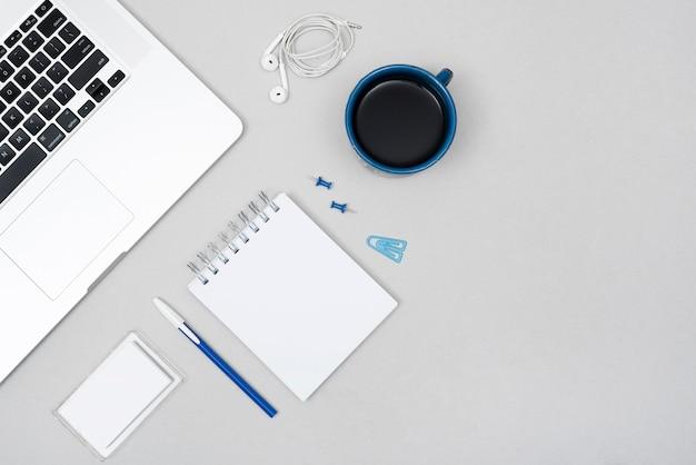 Ordenador portátil; taza de café con papelería de oficina y auricular sobre el escritorio de negocios gris