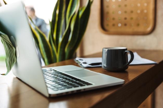 Ordenador portátil con taza y portapapeles en la mesa cerca de la ventana en el café en el interior