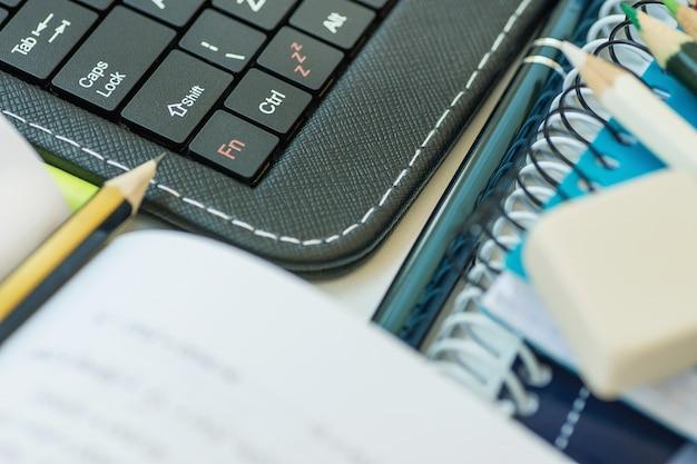 Ordenador portátil, teclado, teclado, libro de texto abierto, pila de cuadernos, bolígrafo, en el escritorio blanco