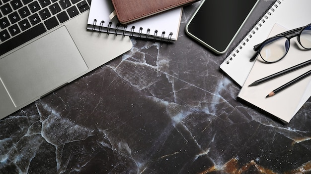 Ordenador portátil, teléfono inteligente y cuadernos de mesa de mármol