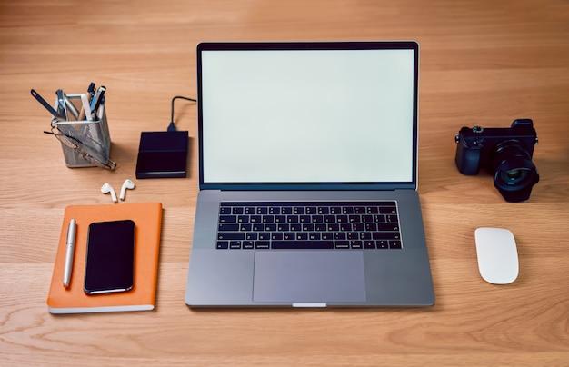 Ordenador portátil y teléfono inteligente en la oficina creativa, pantalla en blanco en maqueta para diseño publicitario.