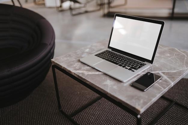 Ordenador portátil y un teléfono en una mesa de mármol.