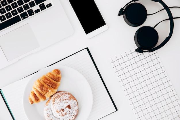Ordenador portátil; teléfono móvil; auricular; papel cuadriculado cuadrado; croissant al horno y bollos en diario sobre fondo blanco