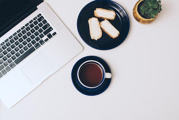 Ordenador portátil; tostadas con queso y café sobre fondo blanco