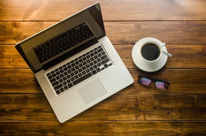Ordenador portátil y taza de café en el piso de madera