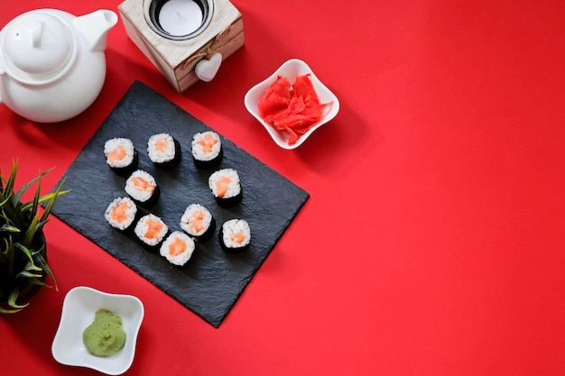Ordene la entrega de rollos de sushi de comida japonesa mientras se queda en casa en cuarentena. forma de casa sobre fondo rojo con espacio de copia