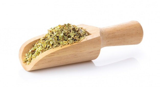Orégano seco en cuchara de madera en blanco