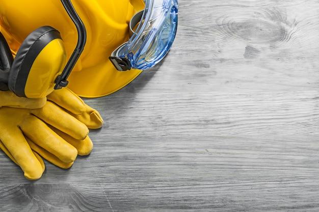 Orejeras gafas protectoras guantes casco en concepto de construcción de tablero de madera