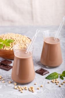 Orgánica leche de chocolate de soja no láctea en vidrio y placa de madera con soja sobre un fondo de hormigón gris.