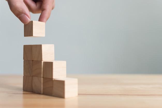 Organización manual de apilamiento de bloques de madera como escalón