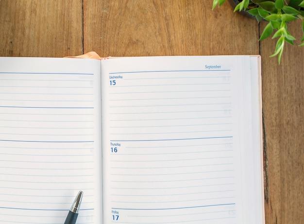 Organizador y pluma en el fondo de la tabla de madera - planificación de negocios.