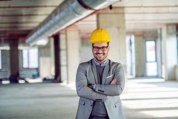 Orgulloso arquitecto caucásico exitoso con casco en la cabeza de pie dentro del edificio que creó. el edificio está en proceso de construcción.