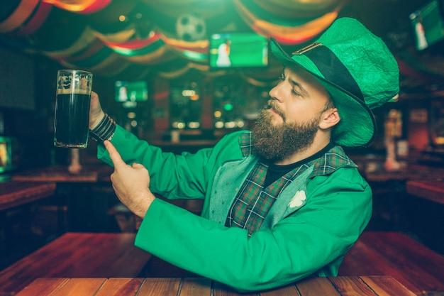 Orgulloso y confiado joven sentado a la mesa en el pub. sostiene una jarra de cerveza oscura y se la muestra a la cámara. joven vistiendo traje de san patricio.