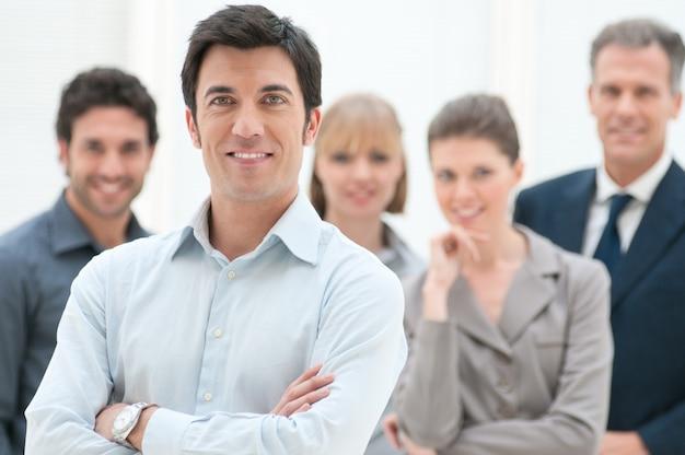 Orgulloso empresario sonriente de pie con sus colegas en la oficina