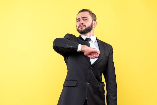 Orgulloso joven está parado y sostiene su codo en amarillo