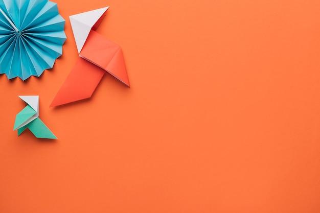 Origami arte de papel artesanal en superficie naranja oscuro