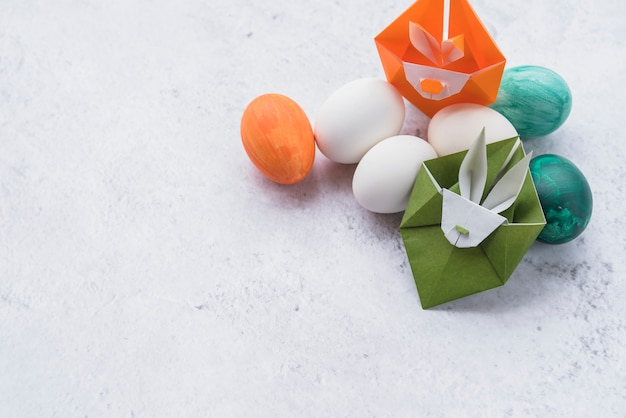 Origami de conejos verdes y naranjas y conjunto de huevos de pascua.