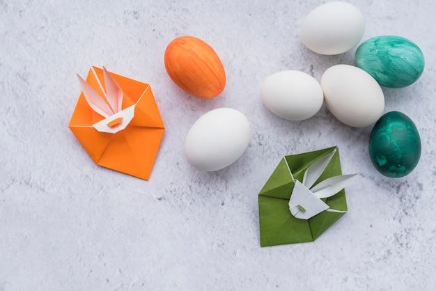Origami de conejos verdes y naranjas y huevos de pascua.