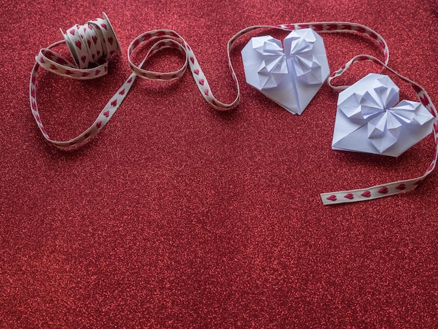 Origami de papel símbolos de forma de corazones para el día de san valentín, con cinta de regalo con corazones rojos. copie espacio para texto o diseño
