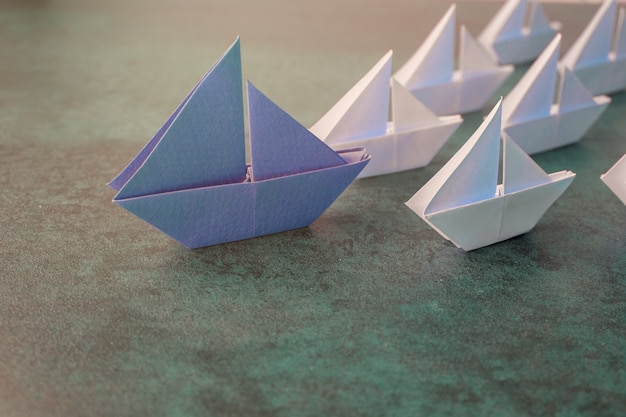 Origami papel veleros, concepto de liderazgo empresarial.