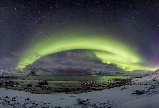 Orilla cubierta de nieve por el agua bajo la hermosa aurora boreal en el cielo estrellado en noruega
