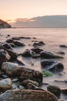 Orilla del mar al amanecer con niebla, playa con grandes piedras