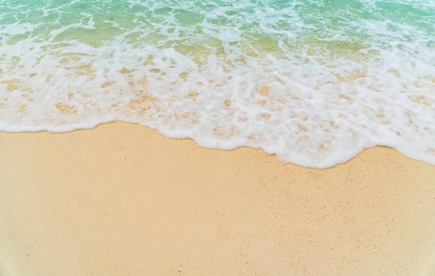 Orilla del mar de arena de la playa con ola azul y fondo blanco espumoso de verano, vista aérea de la playa superior al mar.