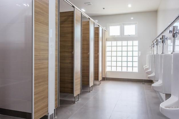 Orinales blancos en el baño público de hombres limpios, vacíos, con ventana grande y luz del exterior.