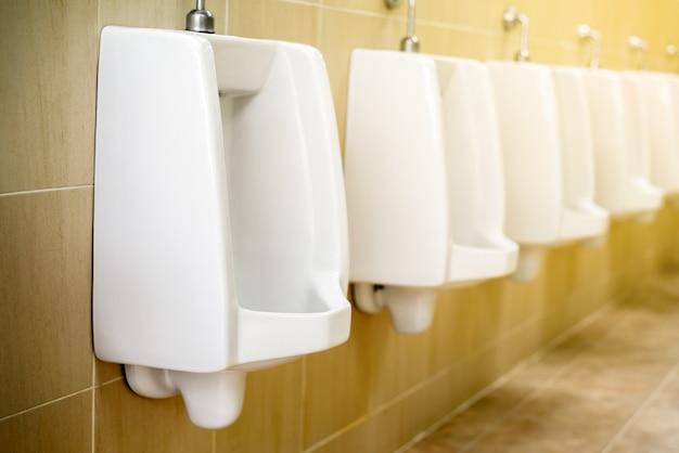 Orinales de cerámica blancos para baño de hombres.