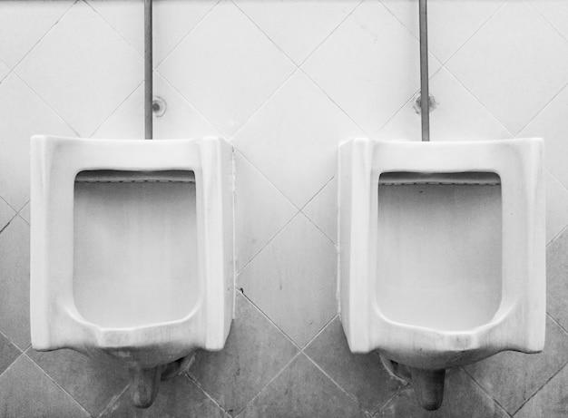 Orinales vintage en baño exterior para hombres.
