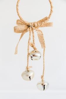 Ornamento de navidad con cascabeles de plata sobre fondo blanco