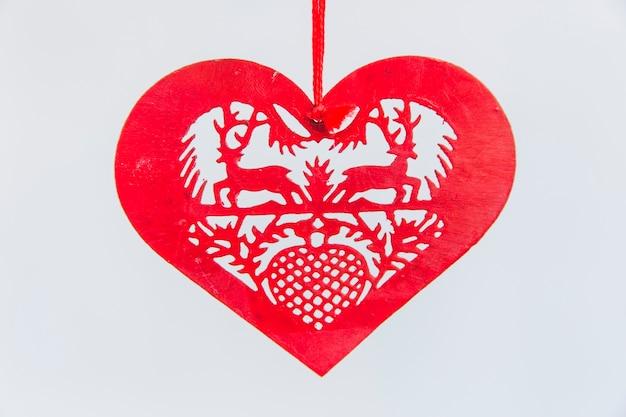 Ornamento rojo de la navidad de la dimensión de una variable del corazón en el fondo blanco