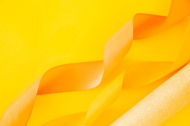 Oro enrollado papel y cinta rizado sobre fondo amarillo