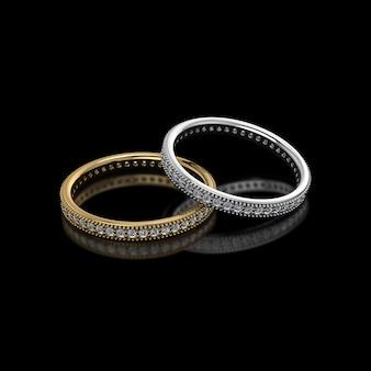 Oro y plata con anillos de boda de diamante sobre fondo negro.