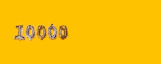 Oro y silvr 10.000 globos número sobre fondo amarillo. seguidores y concepto de suscripción