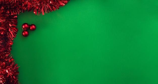 Oropel rojo de navidad con bolas sobre fondo verde. copie el espacio. enfoque selectivo.