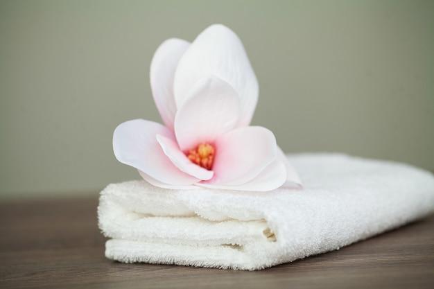 Orquídea de spa con toallas suaves sobre mesa de madera.
