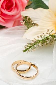 Orquídeas blancas y rosa rosa y anillos de boda.