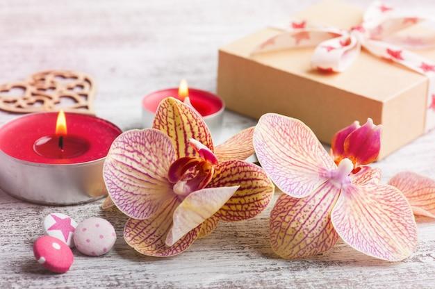 Orquídeas, caja de regalo artesanal y velas encendidas