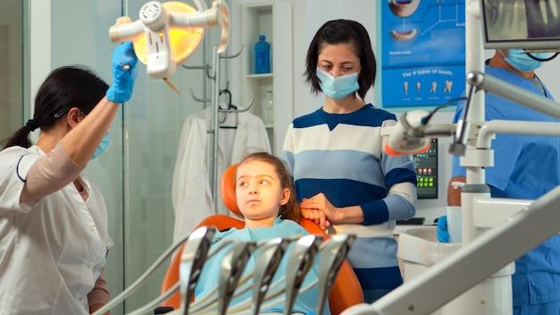 Ortodoncista encendiendo la lámpara hasta examinar al niño y al paciente abriendo la boca. estomatólogo hablando con la madre de una niña con dolor de muelas sentada en la silla de estomatología mientras la enfermera prepara las herramientas.