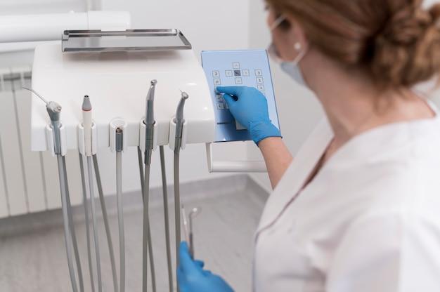 Ortodoncista femenina con guantes de látex manipulando equipos dentales